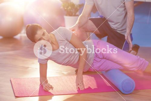 Low section of physiotherapist assisting woman while exercising on exercise mat