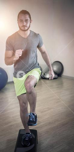 Portrait of serious man doing exercise on aerobic stepper