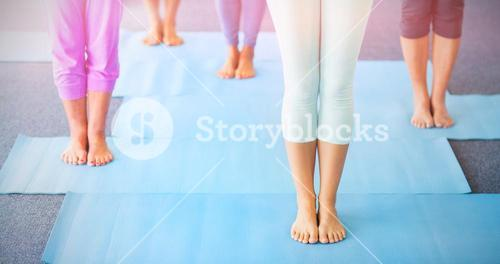 Low section of instructor performing yoga with seniors