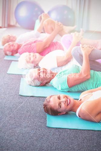 Portrait of instructor performing yoga with seniors