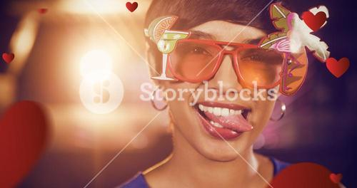 Composite image of woman wearing fancy sunglasses making funny faces in bar
