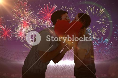 Composite image of geeky hipster couple kissing behind heart card