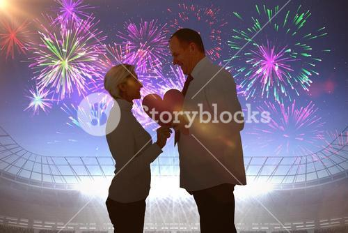 Composite image of older affectionate couple holding pink heart shape