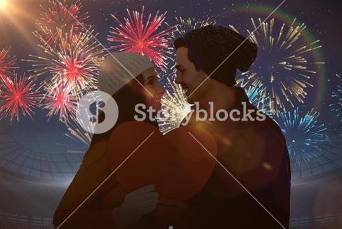 Composite image of happy couple holding paper heart