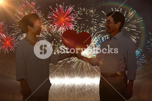Composite image of older asian couple holding heart