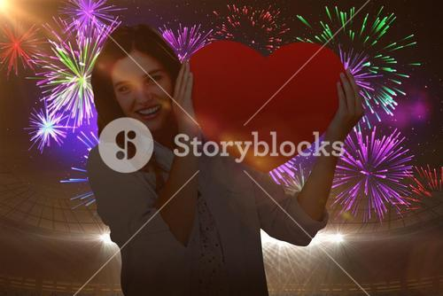 Composite image of woman holding heart card