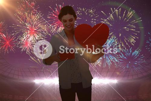 Composite image of woman holding a present and heart card