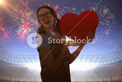 Composite image of geeky hipster woman holding heart card
