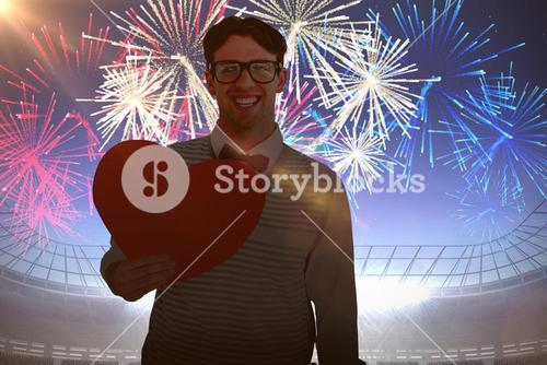 Composite image of geeky hipster holding heart card