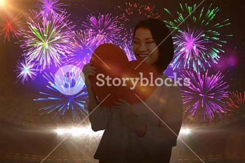 Composite image of woman holding heart shape paper