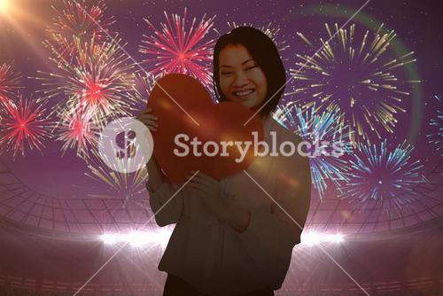 Composite image of happy woman holding heart shape paper