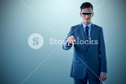 Composite image of businessman pointing while using virtual reality glasses