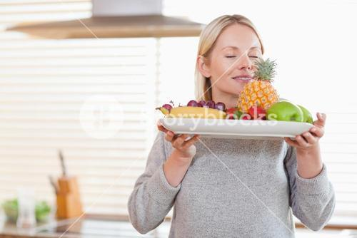 Woman smelling on her fruit plate