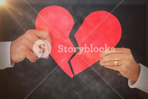 Composite image of couple holding a broken paper heart