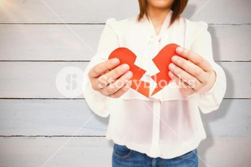 Composite image of woman holding broken heart paper