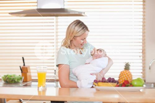 Woman holding her sleeping baby in the kitchen