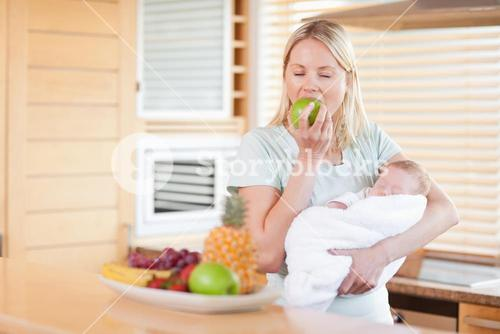 Woman eating an apple while holding her baby