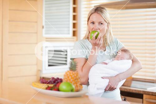 Woman with baby on her arms eating an apple