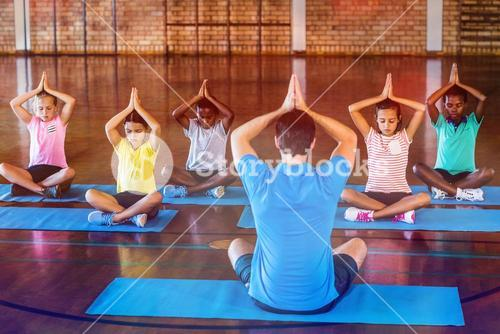 School kids and teacher meditating during yoga class