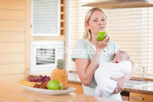 Woman chewing on apple while holding baby on her arms