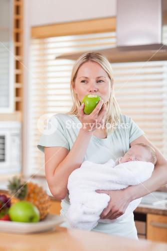 Woman with baby on her arms having an apple