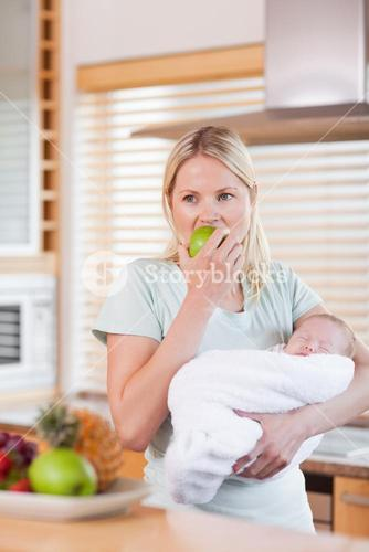 Female with baby on her arm having an apple