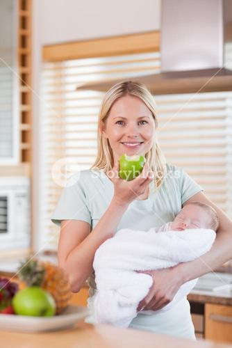Mother with baby on her arms having an apple