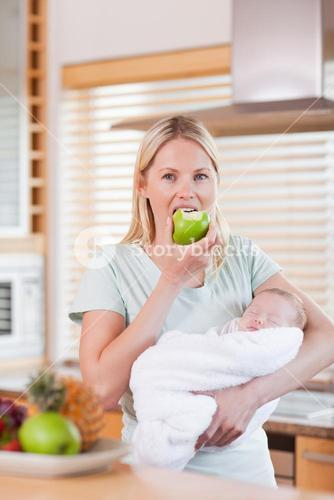 Mother with her newborn having an apple