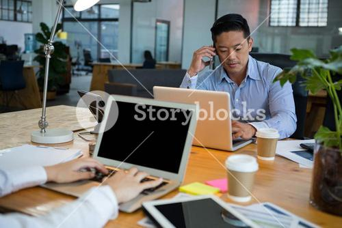 Business executives using laptop at desk
