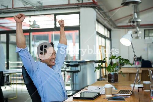 Excited graphic designer looking at laptop