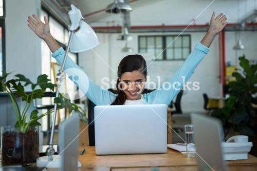 Excited female business executive looking at laptop