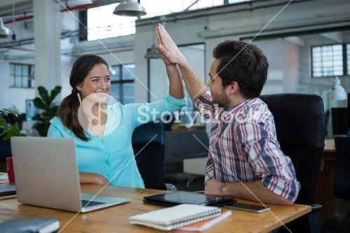 Happy business executives giving high five at desk