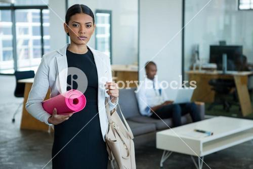 Portrait of businesswoman standing with handbag and exercise mat
