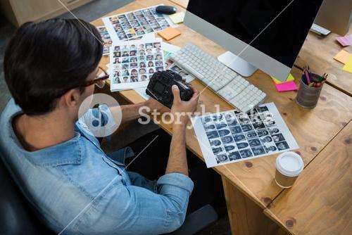 Man sitting at desk holding digital camera