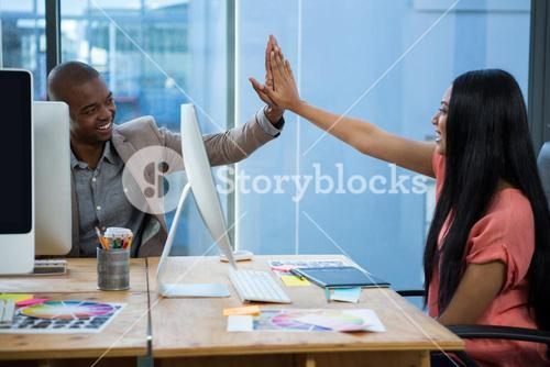 Business executives giving high five each other