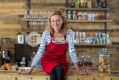 Portrait of waitress sitting at counter