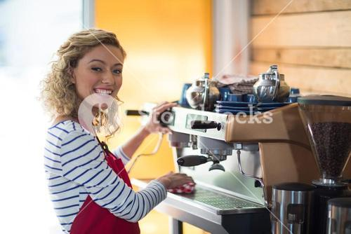 Smiling waitress wiping espresso machine with napkin in café