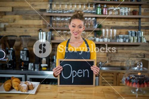 Smiling waitress standing with open sign board in cafe