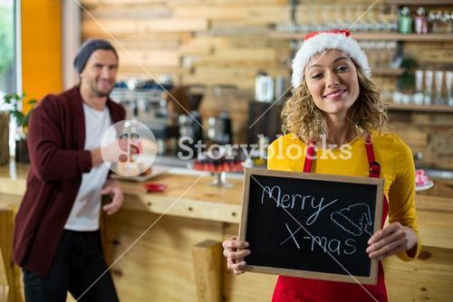 Smiling waitress standing with merry x mas sign board in cafe