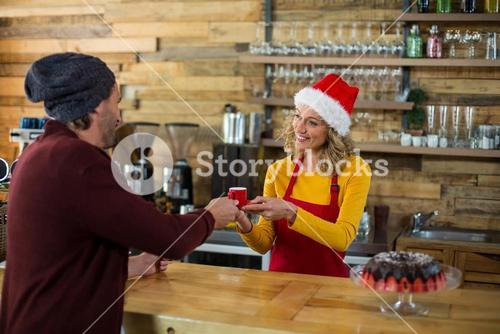 Waitress serving a cup of coffee to customer in café