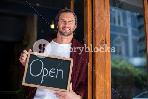 Smiling owner leaning with open sign board in cafe