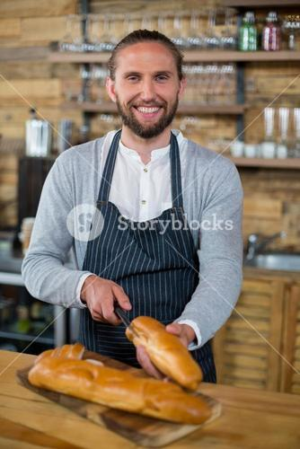 Portrait of waiter cutting bread at counter