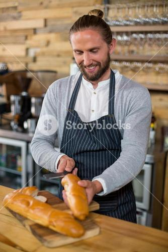 Waiter cutting bread at counter in café