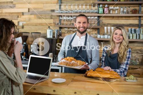 Woman using laptop and waiter and waitress working at counter