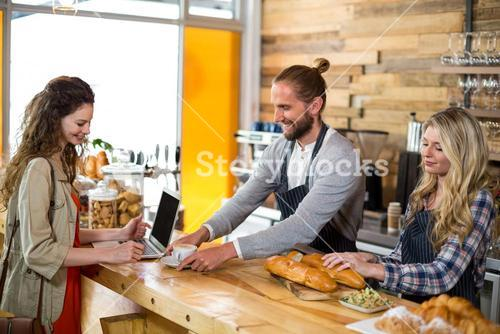 Waiter serving a cup of coffee to customer at counter