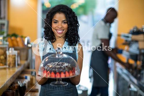 Portrait of smiling waitress holding a cake stand with chocolate cake