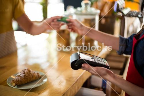 Customer making payment through credit card at counter in café