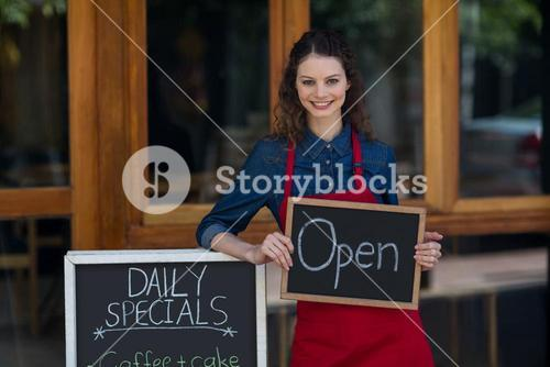 Portrait of waitress standing with chalkboard and menu