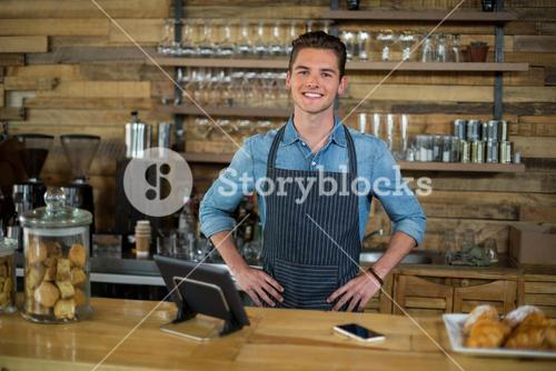 Smiling waiter standing with hands on hip at counter