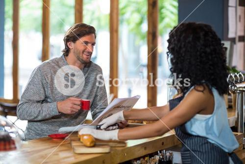 Waitress interacting with customer at counter